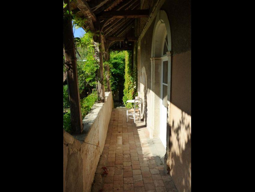 Coursive avec charpente XVIème carrelée de terre-cuite et donnant accès par porte avec imposte ceintrée au logis d'habitation