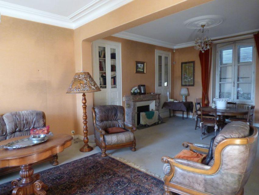 un salon avec plafond mouluré, sol parqueté et cheminée d'époque  en marbre